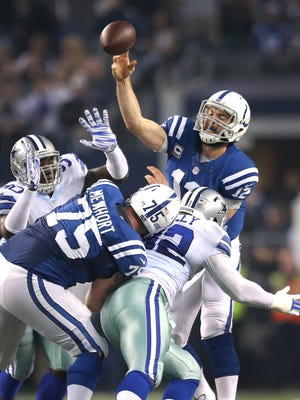 Colts quarterback Andrew Luck gets pressure from Dallas Cowboys defensive end Demarcus Lawrence and teammate Jeremy Mincey as Indianapolis Colts guard Jack Mewhort tries to keep them away, Dec. 21, 2014.