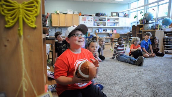 Landon Cooper beams as he receives football swag from