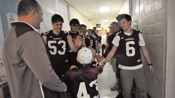 Landon Cooper gets high-fives from Owen football players as he walks the hall at Swannanoa Valley Montessori School