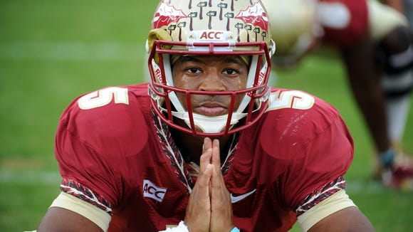 Florida State Seminoles quarterback Jameis Winston warms up before a game against the Syracuse Orange at Doak Campbell Stadium.