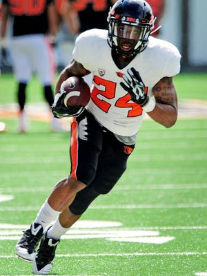 Oregon State running back Storm Woods carries the ball during practice inside Reser Stadium, on Saturday, April 4, 2015, in Corvallis.