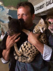 Tim Stark, President of Wildlife in Need & Wildlife in Deed holds a black bear cub and an African Serval. His Charlestown wildife rehabilitation center had a display of animals that they care for.