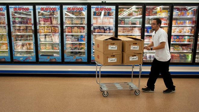 Freddy Rodriguez, of Camden, a meat supervisor at the new PriceRite in Camden, pushes a cart past the frozen seafood section on Tuesday. The new PriceRite will officially open Wednesday; it's the first new grocery store in the city of Camden in 40 years.