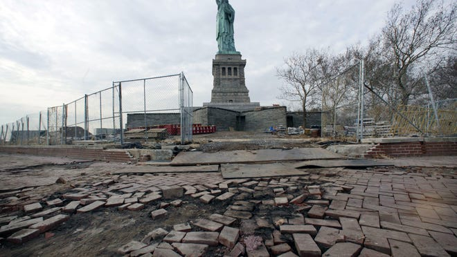 In this Nov. 30, 2012 file photo, the Statue of Liberty stands beyond parts of a brick walkway damaged in Superstorm Sandy on Liberty Island in New York. The National Park Service says $1.51 billion of assets on the island would be highly exposed by a sea level rise of 3 feet.