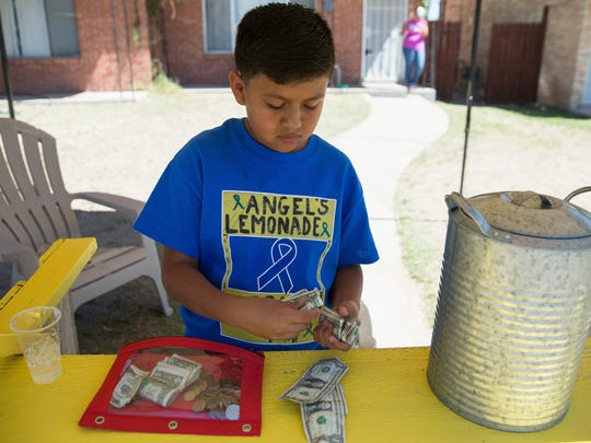 Angel Reyes,9, collects the money he has earned from selling lemonade at his lemonade stand. Reyes hopes to raise about 100 dollars to help with his grandfathers cancer treatment, Wednesday, March 22, 2017.