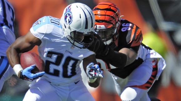 Titans running back Bishop Sankey has his face mask pulled by Bengals defensive end Carlos Dunlap during the third quarter at Paul Brown Stadium.