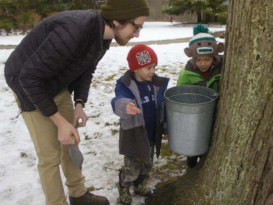 Assistant naturalist Chris Long and visitors Tobias and his brother Elijah Slinde inspect a sap bucket at Heritage Park.