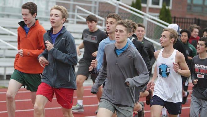From left in the front row, Will Blasdell, Aidan McDermott, Drew Dorflinger, Dylan Bronkema, Jean-Christophe Yahia and Robert Feeney run a warm-up lap around the track at Pleasantville High School on Thursday.