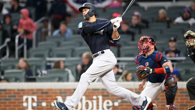 Yankees left fielder Giancarlo Stanton hits a home run against the Atlanta Braves in the third inning at SunTrust Park.