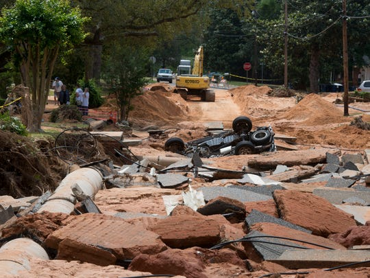 Work crews repair damage to Blue Springs Avenue in the Crescent Lake neighborhood after flooding in April 2014 devastated the area.
