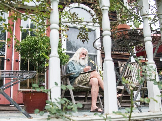 Gavin Dillard works on some poetry on the porch on