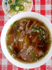 The marbled brisket pho is topped off with scallions
