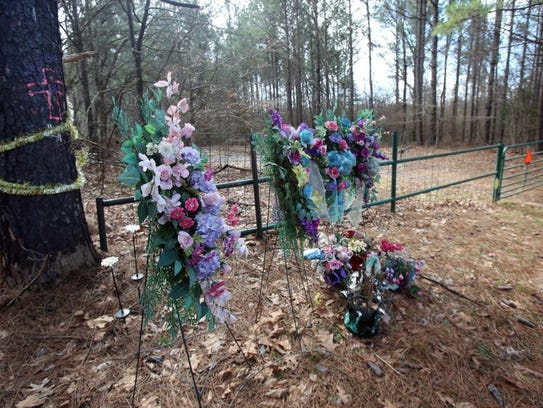 Flowers, ribbon and a painted cross mark the desolate