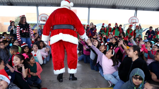 Santa Claus is greeted by students as they arrive for Christmas Around the World at Hicks Elementary School on Thursday, December 14, 2017.