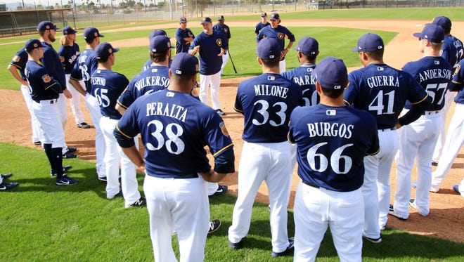 A group of Brewers pitchers listen to Ed Sedar and Carlos Subero during spring training drills Friday. The Brewers are hoping many of their players take another step forward in the team's rebuilding plan.