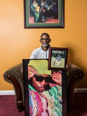 Michael Thomas holds photos of his son Michael, on