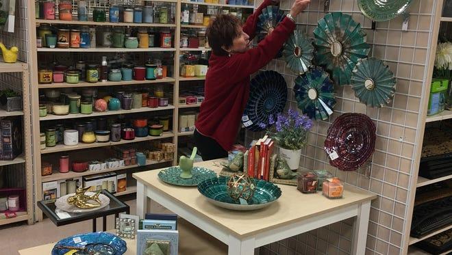 "Bobbie Brister adjusts one of her patented ""end cap"" displays that help brighten the sales floor at Burkes."