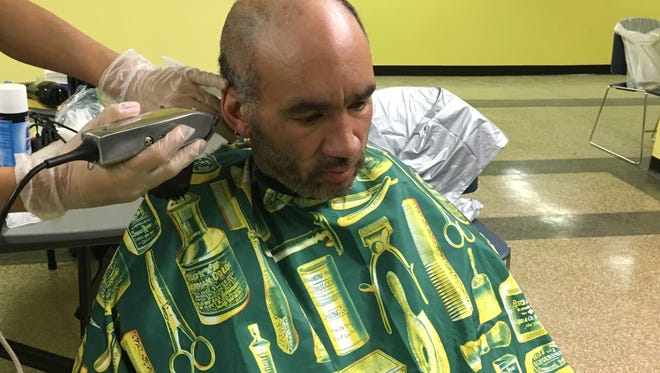 Sean Robinson, a homeless man who lives in Perth Amboy, gets a free haircut at the Family Life Center of Cathedral International.
