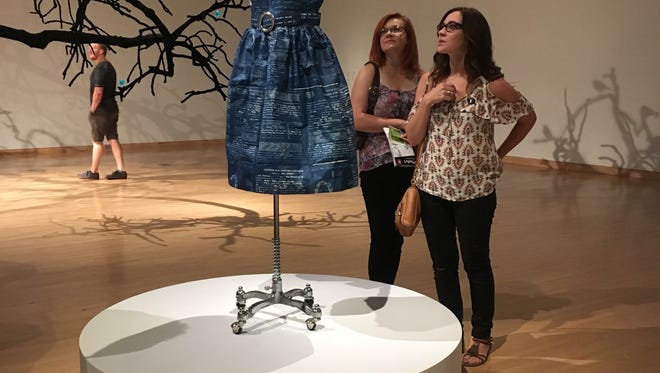 """Museum patrons check out local Annie Lopez's """"Naturalized Citizens"""" at the Phoenix Art Museum on July 6, 2018. Lopez crafted the dress out of tamale papers printed with her family's naturalization documents."""