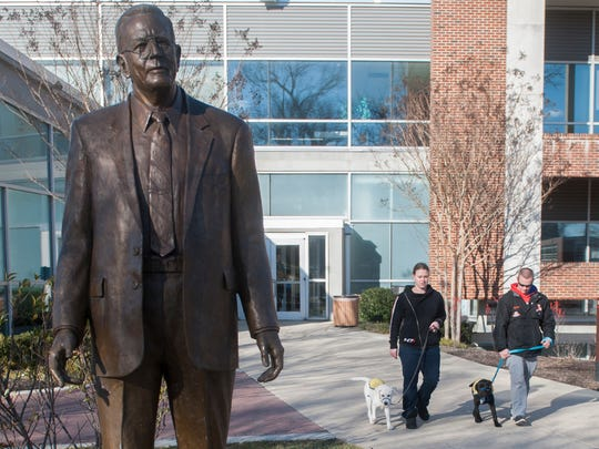 Rowan junior Jim Witkoski of Marlton, right, walks a 4-month-old lab named Augie as Rowan senior Nicole Puzio of Medford walks a 4½-month-old mix named Treat near  a statue of Henry Rowan on the campus of Rowan University in Glassboro.  The two Rowan students are puppy raisers for Canine Companions for Independence.  02.26.16