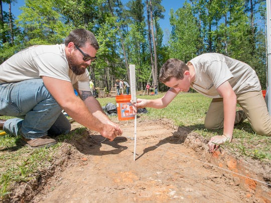 University of West Florida archaeology graduate Kenyan Murrell, left, and Milton High School freshman Owen Williamson take a measurement during the Milton High School archaeology class excavation at the Scott Site in Milton on Friday, April 7, 2017.