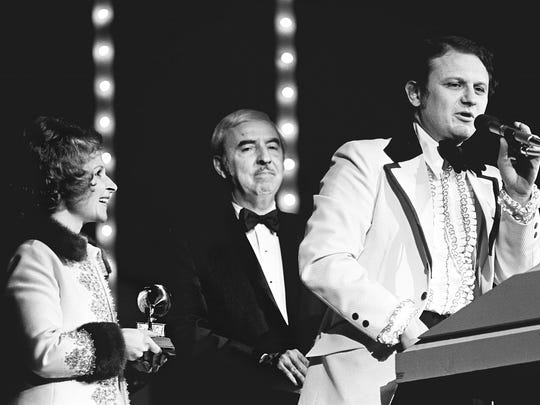 Charlie McCoy, right, accepts the Grammy award for Best Country Instrumental Performance during the champagne breakfast and the final 36 presentations of the Grammy awards at the Municipal Auditorium after the nationally televised show March 4, 1973. Co-host Brenda Lee, left, and Presenter Fred Rose looks on.