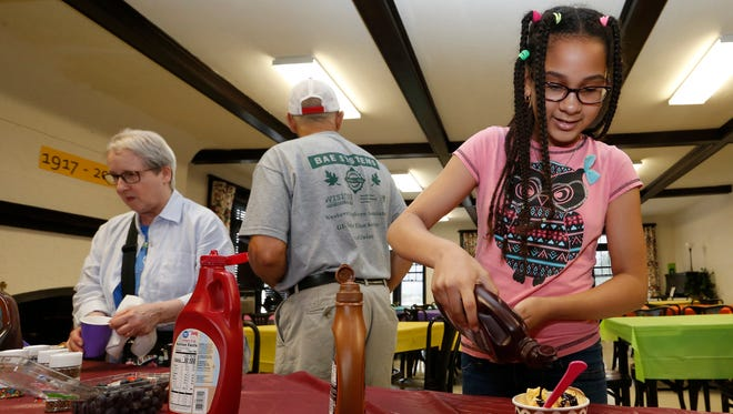 Bridget Cronin adds chocolate syrup to her dish of ice cream during an ice cream social held at Your Home Public Library in Johnson City on July 13.