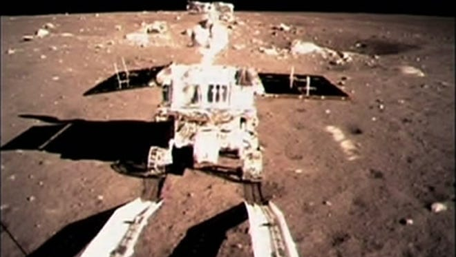 """In this image taken by the onboard camera of the lunar probe Chang'e 3 and made off the screen of the Beijing Aerospace Control Center in Beijing, China's first moon rover, """"Jade Rabbit,"""" touches the lunar surface Dec. 15, 2013."""
