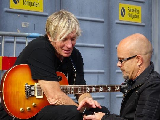 Louisville native Dallas Schoo talks guitars with a fan before a U2 show.