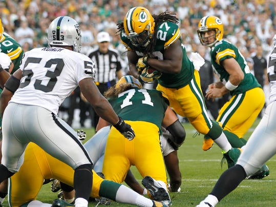 Green Bay Packers running back Eddie Lacy (27) dives into the end zone for a touchdown as Oakland Raiders middle linebacker Nick Roach (53) defends during the first half of an NFL preseason football game Friday, Aug. 22, 2014, in Green Bay, Wis. (AP Photo/Mike Roemer)