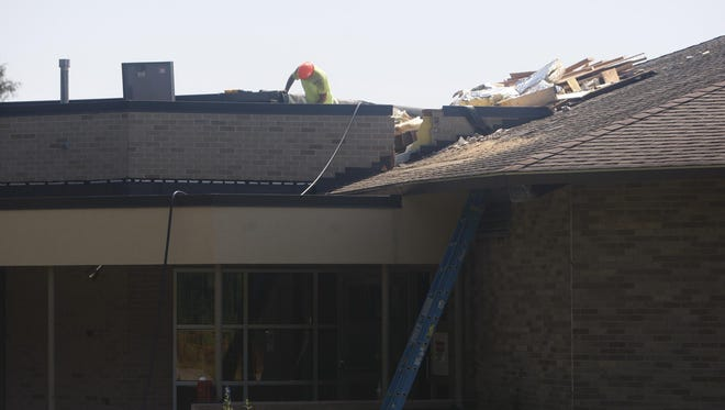 Crews work Tuesday at St. Pius Tenth, 3000 Chili Ave. in Chili, as demolition work begins after a January fire.