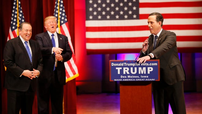 Republican presidential candidates Mike Huckabee and Donald Trump laughs as Republican presidential candidate Rick Santorum jokes about not being photographed in front of a Trump podium sign during an event at Drake Thursday, Jan. 28, 2016.