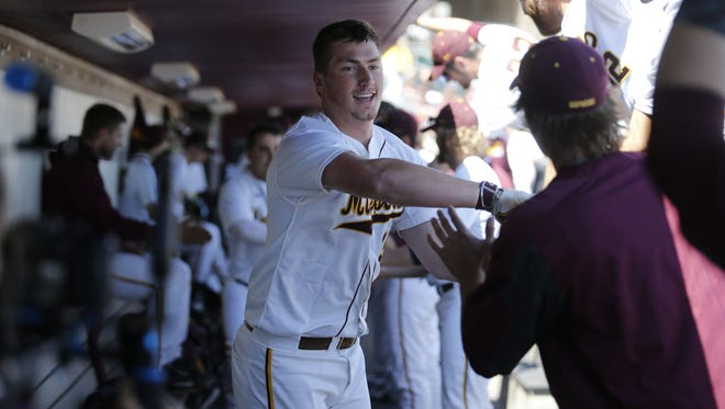 Rocori grad and Minnesota Gophers catcher Austin Athmann high-fives teammates during a game this season.