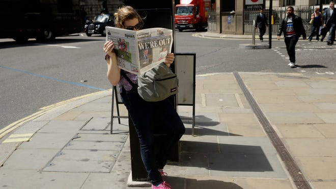 A woman reads a copy of the London Evening Standard newspaper outside the Bank of England in the City of London on Friday, the day after Britons voted to exit the European Union.