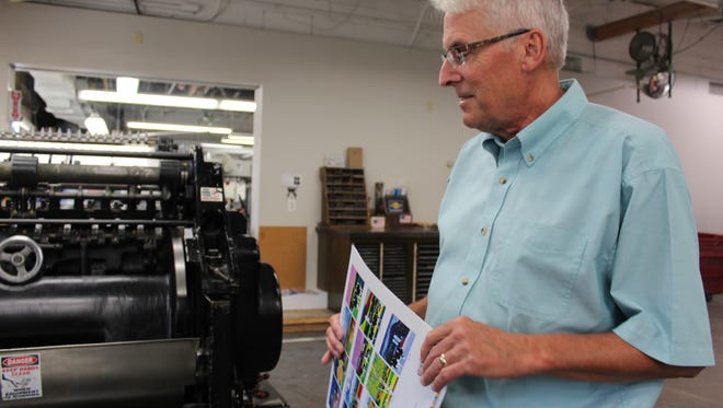 Alan Schillhammer, owner of Queen City Printers, holds a calendar while explaining how a scoring machine works  on Thursday.