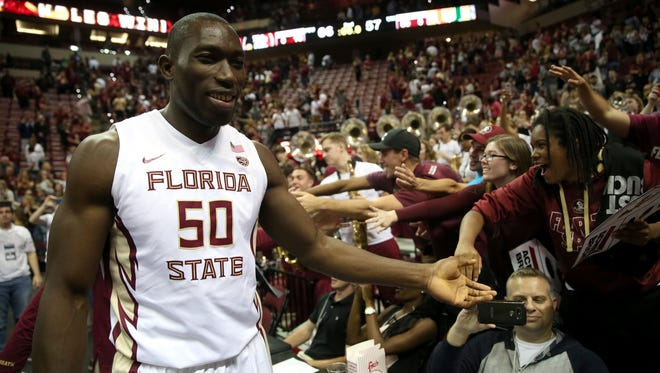 FSU's Michael Ojo high-fives fans on his way off the court after their 66-57 win against Miami at the Tucker Civic Center on Saturday.