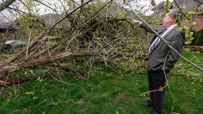 Steve Vaught looks at the tree that was knocked down in his front yard by a strong storm on the 5100 block of Greenbriar Avenue on Wednesday, April 4, 2017. It appeared that there was only minor damage to the gutter on the home.