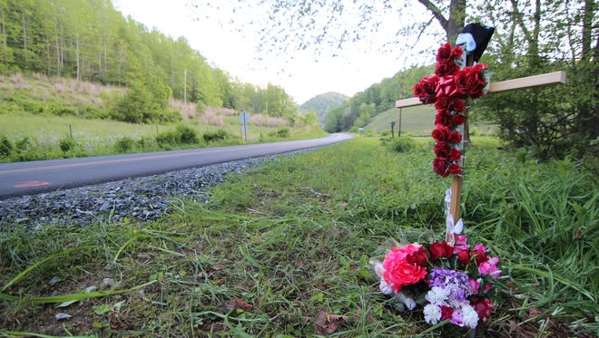 Flowers and a wooden cross were placed beside Grapevine Road in remembrance of Angela Cody.
