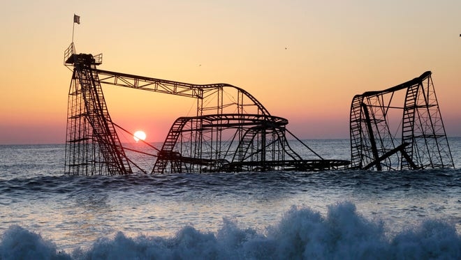 In this Feb. 25, 2013, file photo, the sun rises behind the Jet Star Roller Coaster, sitting in the ocean after part of the Funtown Pier was destroyed during Superstorm Sandy, in Seaside Heights, N.J.