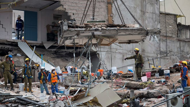 A crane removes a slab of concrete at the site of a felled office building brought down by a 7.1-magnitude earthquake, in the Roma Norte neighborhood, in Mexico City, Sept. 23, 2017.