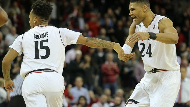 Cincinnati Bearcats forward Kyle Washington (24) and guard Cane Broome celebrate a made basket in the second half of UC's 80-70 comeback win over Houston on Wednesday.