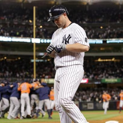 Yankees catcher Brian McCann (34) walks off as the