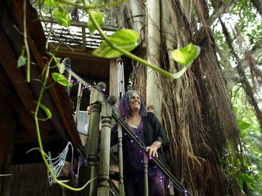 In this Monday, Sept. 19, 2016 photo, Shawnee Chasser stands on the staircase of her treehouse in Miami. Chasser has lived in this treehouse for a decade. Before that, she lived for 15 years in another one on property owned by her brother in nearby Little Haiti after deciding she simply did not like living in air conditioning. (AP Photo/Lynne Sladky)