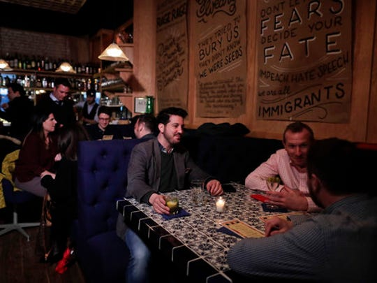 Customers at Coup have drinks shortly after the doors opened, Tuesday, April 25, 2017, in New York. As a response to the Trump Administration, the bar in Manhattan's East Village offers patrons the chance to put their money where their politics are by earmarking where the profits should go from a range of liberal or progressive options like the American Civil Liberties Union or Planned Parenthood.