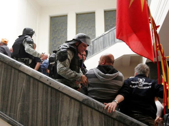 Police try to block protestors as they enter into the parliament building in Skopje, Macedonia, Thursday, April 27, 2017. Scores of protesters have broken through a police cordon and entered Macedonian parliament to protest the election of a new speaker despite a months-long deadlock in talks to form a new government.
