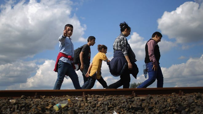 Migrants and refugees cross the border from Serbia into Hungary along the railway tracks close to the village of Roszke on Sept. 6, in Hungary.