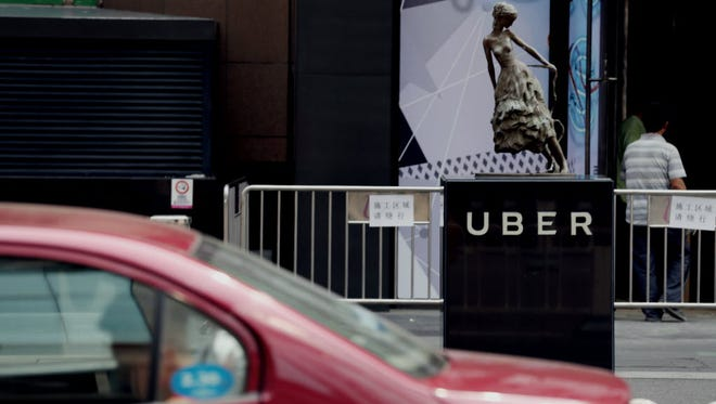 A taxi passes by an Uber station outside a shopping mall in Beijing on August 1.