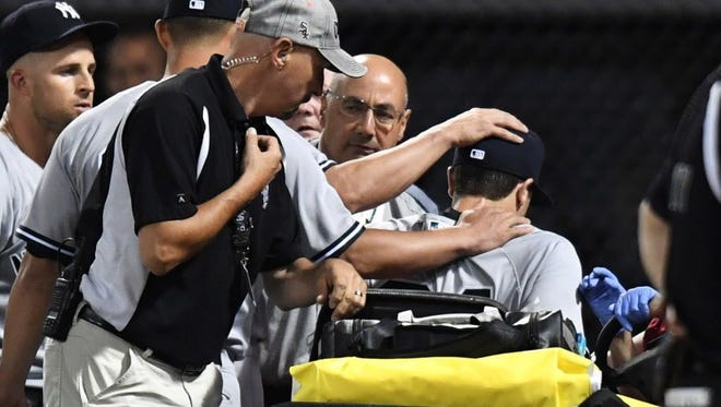 Players place their hands on New York Yankees right fielder Dustin Fowler while being taken off the field after colliding with the wall in the first inning against the Chicago White Sox at Guaranteed Rate Field.