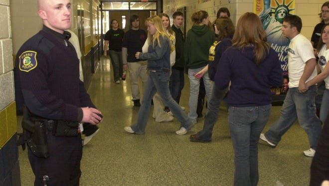 A police officer watches as students walk to classes at Capac High School in 2003.