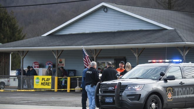 Officialsalong Indian Creek Valley Road after a deadly shooting Sunday, Jan. 28, 2018, in Saltlick Township, Pa. State police said Timothy Smith opened fire early Sunday morning at Ed's Car Wash, killing several. (Stephanie Strasburg/Pittsburgh Post-Gazette via AP)